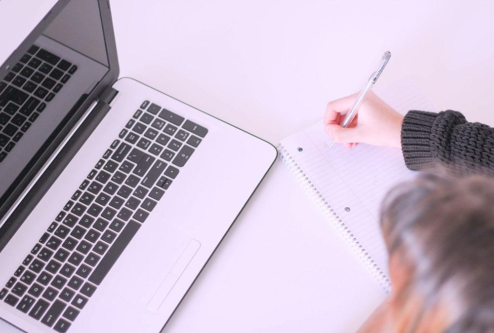 Donna scrive su quaderno con laptop
